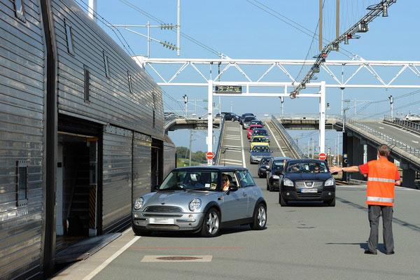 Автомобили заезжают в грузовой поезд.